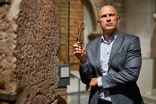 Homem do retrato olhando para a arte em pé na galeria de arte ou museu, copie o espaço