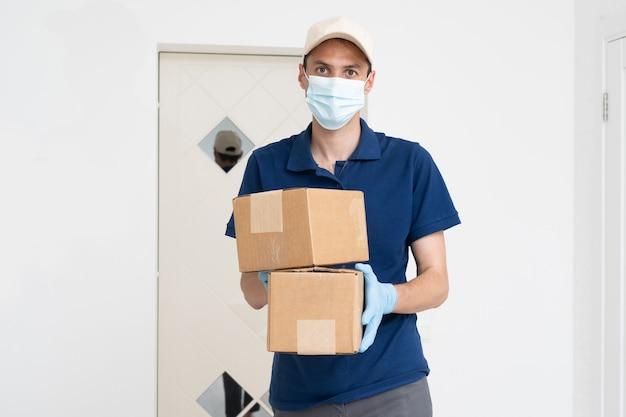 Homem do serviço de entrega em t-shirt, máscara protetora e luvas, dando o pedido de comida e segurando caixas sobre fundo branco.