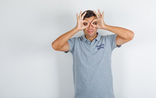 Homem do serviço técnico em camiseta cinza, mostrando gesto de óculos e parecendo engraçado