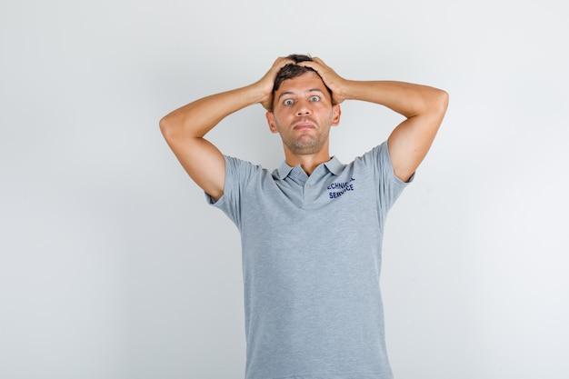 Homem do serviço técnico em camiseta cinza segurando a cabeça com as mãos e parecendo cansado