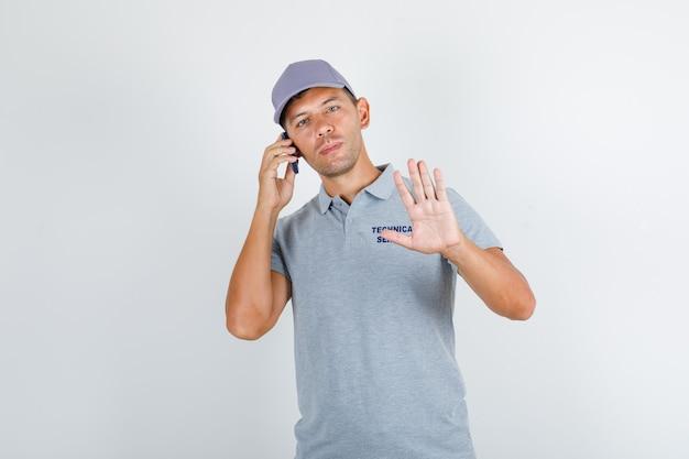 Homem do serviço técnico falando ao telefone sem gestos, em camiseta cinza com tampa
