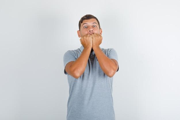 Homem do serviço técnico mordendo os punhos em uma camiseta cinza e parecendo nervoso