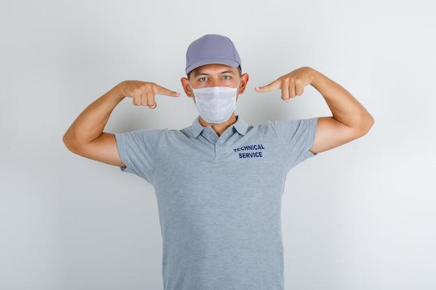 Homem do serviço técnico mostrando máscara médica em camiseta cinza com boné e olhando com cuidado