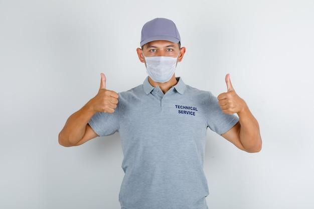 Homem do serviço técnico mostrando os polegares para cima em uma camiseta cinza com boné e máscara médica e parecendo cuidadoso