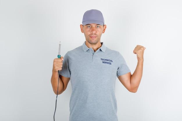 Homem do serviço técnico segurando uma chave de fenda e apontando para trás em uma camiseta cinza com tampa