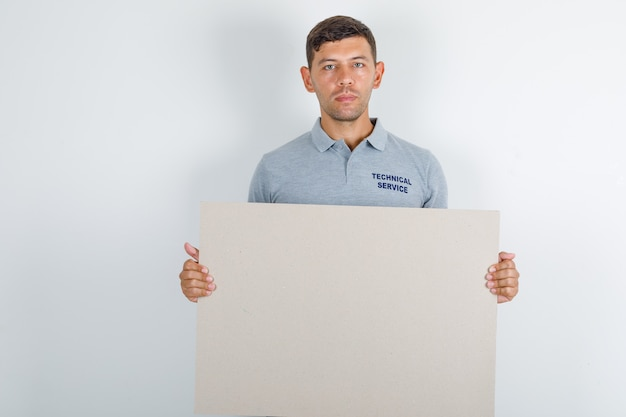 Homem do serviço técnico segurando uma tela e procurando um bom espaço livre para seu texto