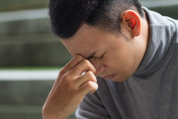 Homem do sudeste asiático doente com dor de cabeça, depressão, estresse