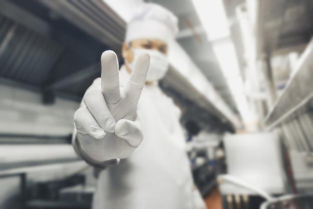 Homem do sudeste da ásia vestindo uniforme de cozinheiro profissional e chapéu com máscara, sorrindo, olhando para a câmera, mostrando os dedos fazendo sinal de vitória. número dois.
