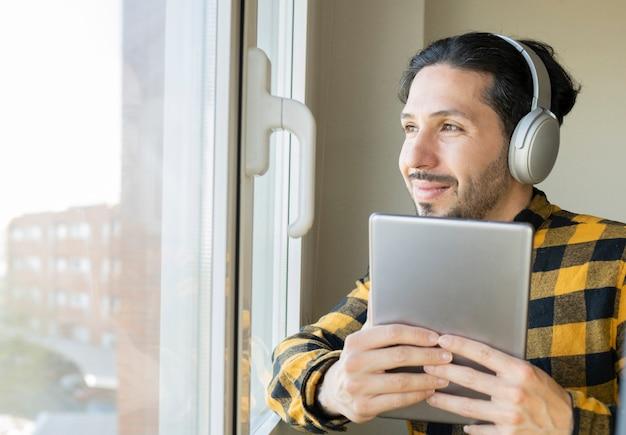 Homem do tablet ao lado de uma janela ouvindo música