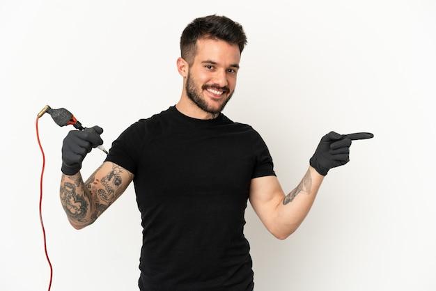 Homem do tatuador sobre fundo branco isolado apontando o dedo para o lado