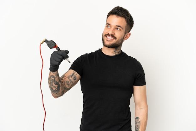 Homem do tatuador sobre fundo branco isolado pensando uma ideia enquanto olha para cima