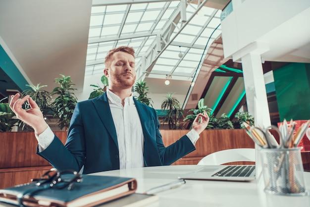 Homem do trabalhador no terno que medita na mesa no escritório.