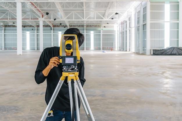 Homem do trabalhador que faz a medição com equipamento do teodolito no canteiro de obras.
