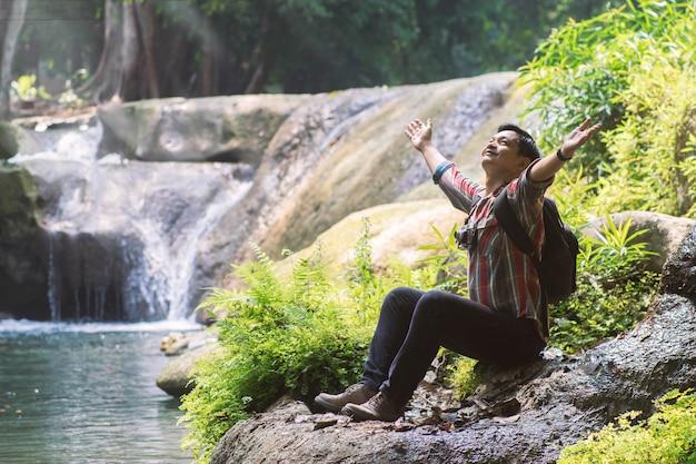 Homem do viajante com a trouxa que guarda a câmera com fundo natural verde.