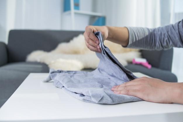 Homem dobrando roupas na mesa Foto gratuita