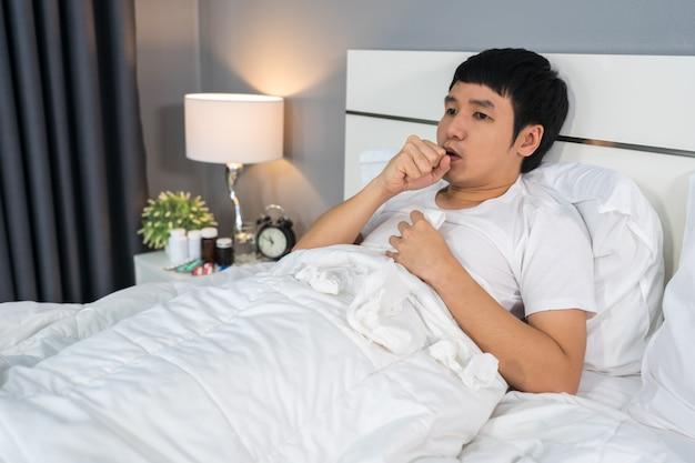 Homem doente, cansado e tossindo na cama