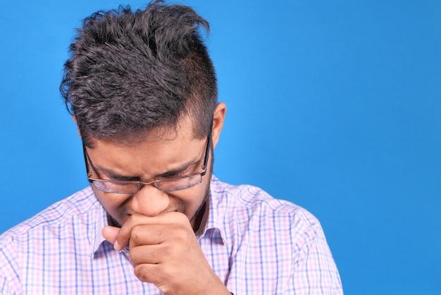 Homem doente com alergia a gripe, espirra e assoa o nariz.