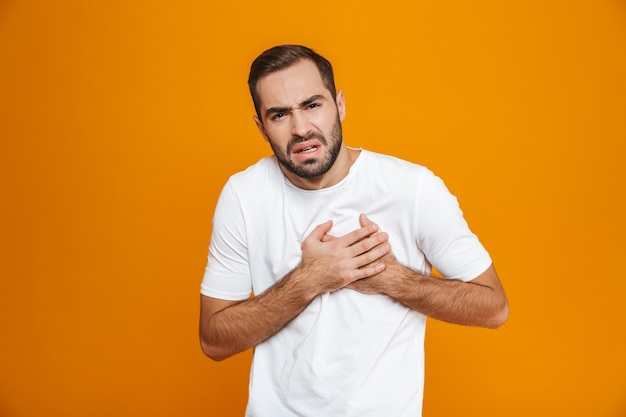 Homem doente com camiseta tocando o coração por causa da dor enquanto, isolado no amarelo
