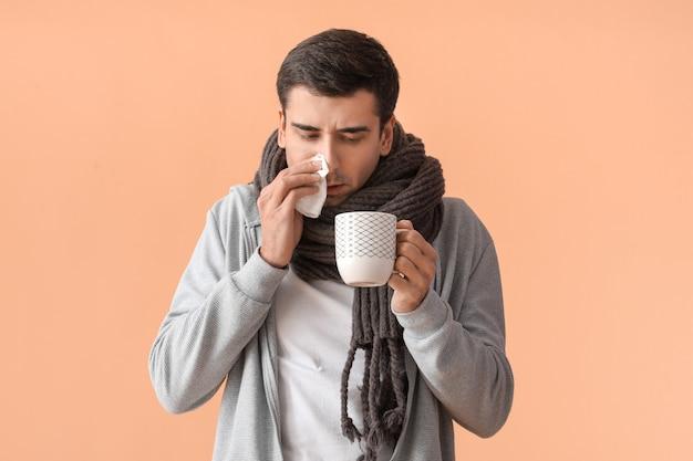 Homem doente com chá quente na superfície colorida