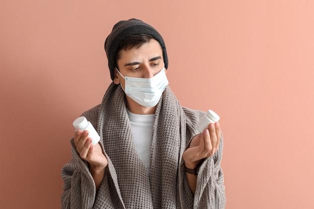Homem doente com comprimidos na superfície colorida