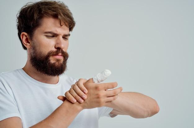 Homem doente com curativo ferimento na mão nos dedos luz de fundo