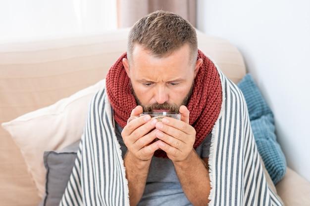 Homem doente, com febre, bebendo chá quente de cura