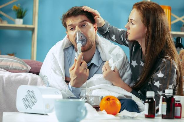 Homem doente com febre deitado na cama com temperatura. a esposa dele cuida dele. a doença, a gripe, a dor, o conceito de família. relaxamento em casa. conceitos de saúde.