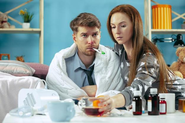 Homem doente com febre deitado na cama com temperatura. a esposa dele cuida dele. a doença, a gripe, a dor, o conceito de família. relaxamento em casa
