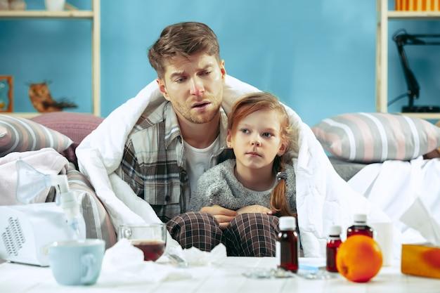 Homem doente com filha em casa. tratamento em casa. lutando com uma doença. saúde médica.