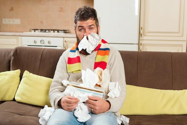 Homem doente com guardanapos de papel assoar nariz. homem contrai gripe, com corrimento nasal.