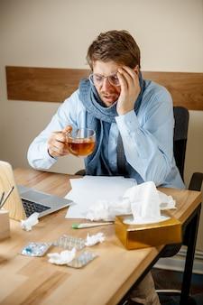 Homem doente com lenço, espirrando, assoando o nariz enquanto trabalhava no escritório