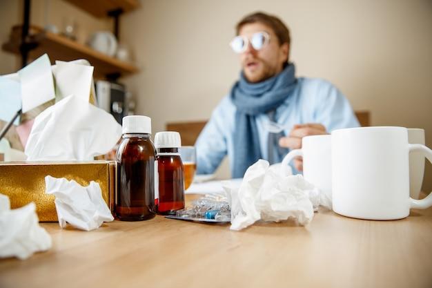 Homem doente com mistura medicinal trabalhando em escritório