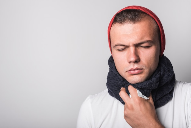 Homem doente com os olhos fechados, sofrendo de frio e tosse contra fundo branco
