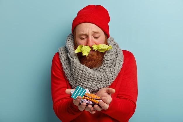 Homem doente com roupas quentes, lenços de papel no nariz e comprimidos