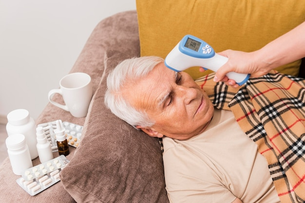 Homem doente com tiro médio deitado no sofá