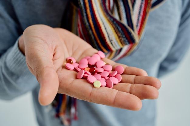 Homem doente com um suéter e comprimidos nas mãos, problemas de saúde, luz de fundo