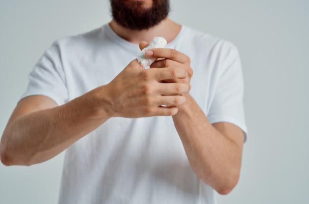 Homem doente com uma camiseta branca e uma luz de fundo com as mãos enfaixadas