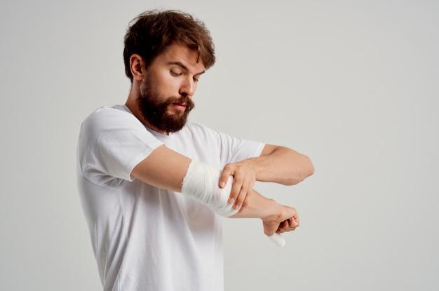 Homem doente com uma camiseta branca e uma mão enfaixada posando com remédio hospitalar