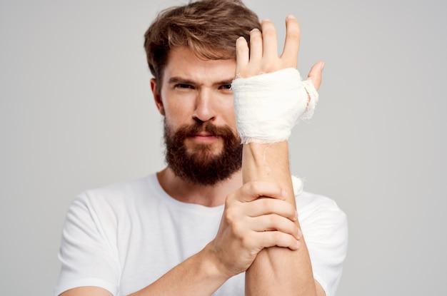 Homem doente com uma camiseta branca e uma mão enfaixada posando com um fundo isolado