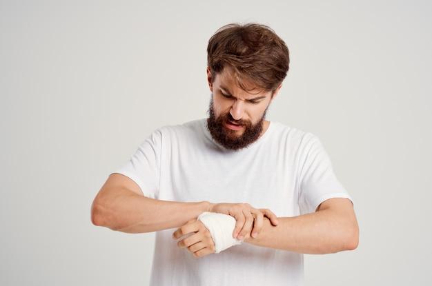 Homem doente com uma camiseta branca e uma mão enfaixada posando de fundo claro