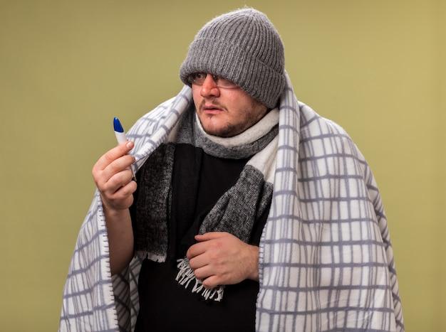 Homem doente de meia-idade assustado usando chapéu de inverno e lenço embrulhado em xadrez segurando e olhando para o termômetro isolado na parede verde oliva