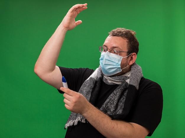 Homem doente de meia-idade assustado usando máscara médica e lenço segurando um termômetro e levantando a mão
