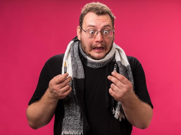 Homem doente de meia-idade com medo, segurando um lenço, segurando e olhando para uma seringa com uma ampola