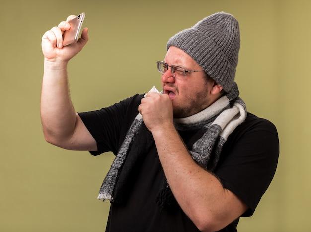 Homem doente de meia-idade com tosse e chapéu de inverno e lenço tira uma selfie isolada na parede verde oliva