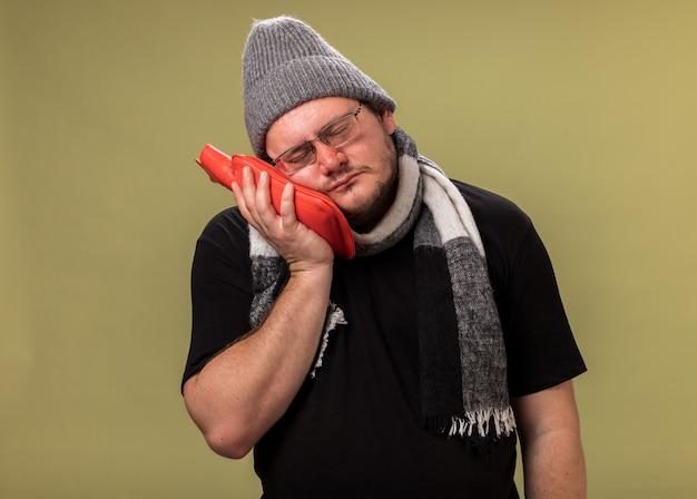 Homem doente de meia-idade, fraco inclinando a cabeça e usando chapéu de inverno e cachecol e colocando uma bolsa de água quente na bochecha