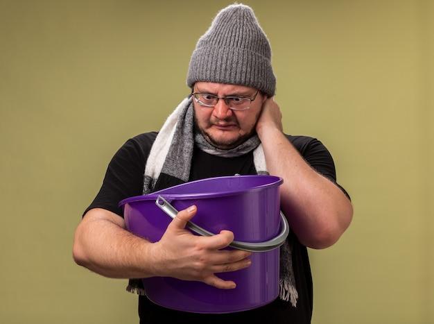Homem doente de meia-idade insatisfeito com chapéu de inverno e lenço segurando e olhando para um balde de plástico colocando a mão no pescoço isolado na parede verde oliva