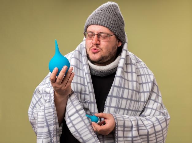 Homem doente de meia-idade satisfeito com chapéu de inverno e lenço embrulhado em xadrez, segurando e olhando para enemas isolados na parede verde oliva