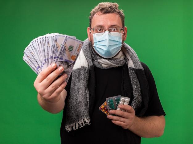 Homem doente de meia-idade usando máscara médica e lenço isolado na parede verde