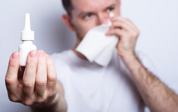 Homem doente detém gotas para o nariz