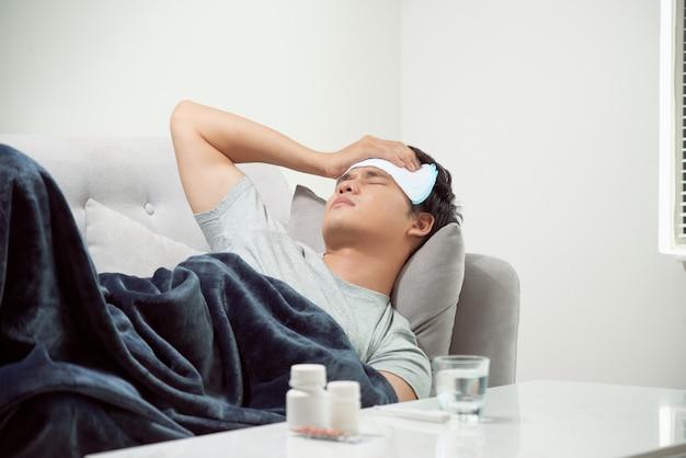 Homem doente e desperdiçado deitado no sofá, sofrendo de resfriado e vírus da gripe de inverno, tendo comprimidos de medicamento no conceito de saúde, procurando temperatura no termômetro